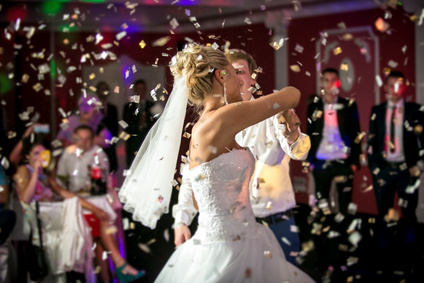 Beautiful blonde bride dancing at restaurant in flying confetti